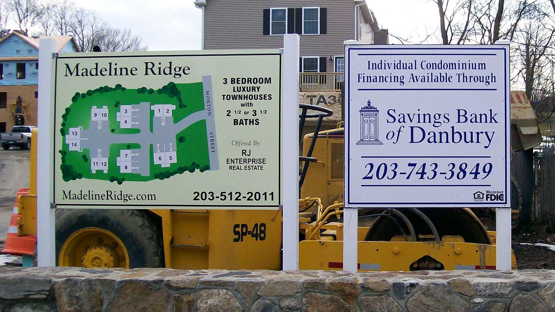 Two site signs on a stone wall