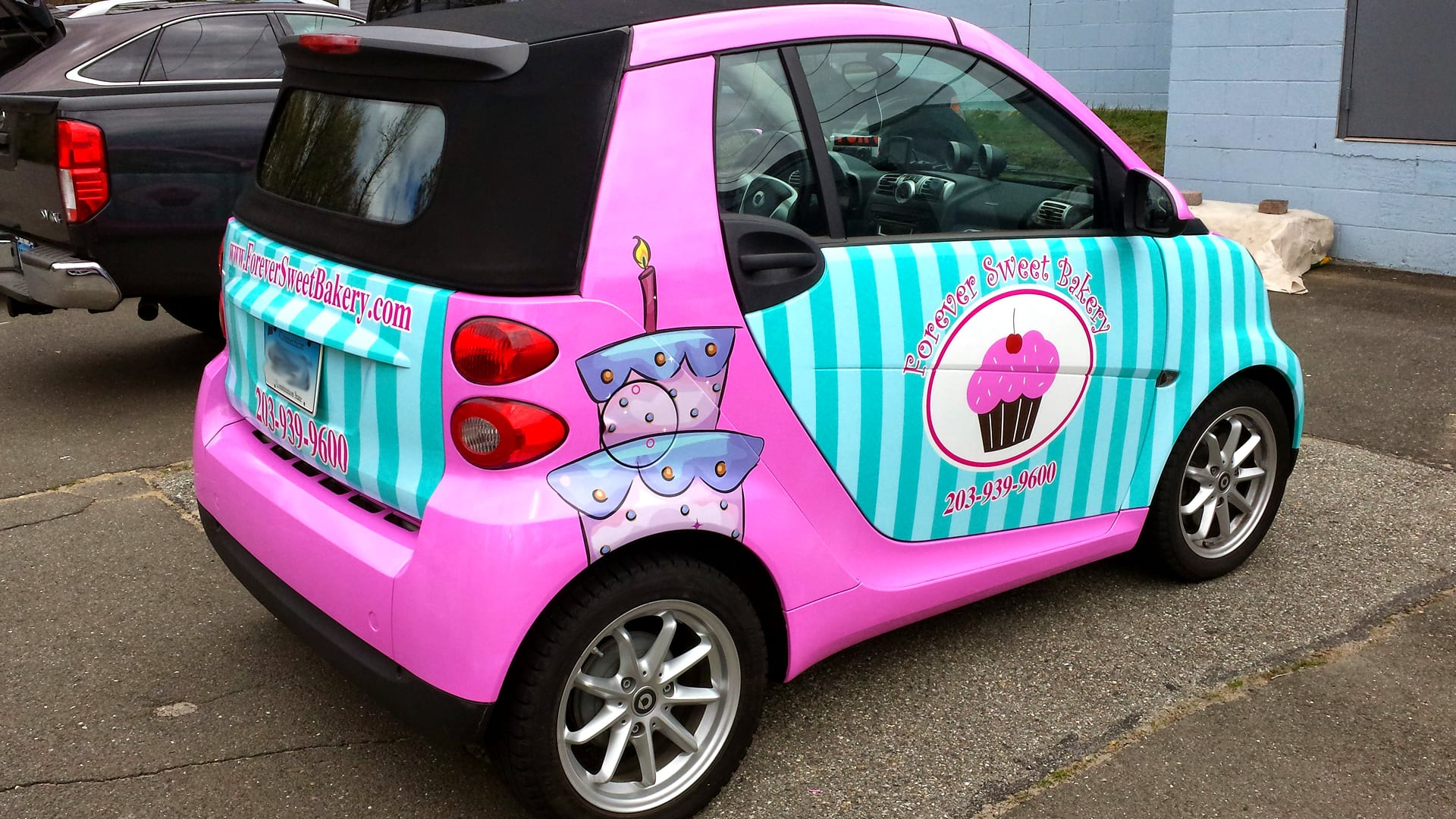 Colorful car wrap advertising a business on a Smart Car